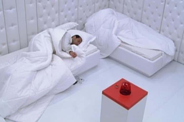 participante dormindo no quarto branco